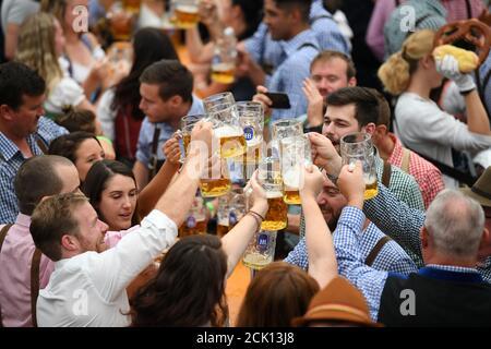 Les visiteurs applaudissent avec des bières dans une tente lors de l'Oktoberfest à Munich, Allemagne, le 22 septembre 2019. REUTERS/Andreas Gebert
