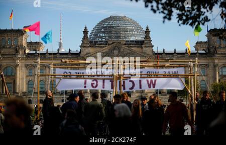 Des gens entrent dans un camp de fortune mis en place par les activistes climatiques de la rébellion des extinction (XR) à côté du bâtiment du Reichstag à Berlin, en Allemagne, le 6 octobre 2019. REUTERS/Hannibal Hanschke