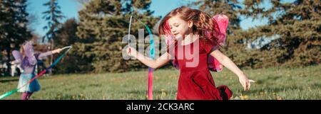 Enfants heureux filles jouant avec des rubans dans le parc. Adorables enfants qui s'amusent dans un pré et qui jouent ensemble. Activité extérieure de jardin d'été pour les enfants.