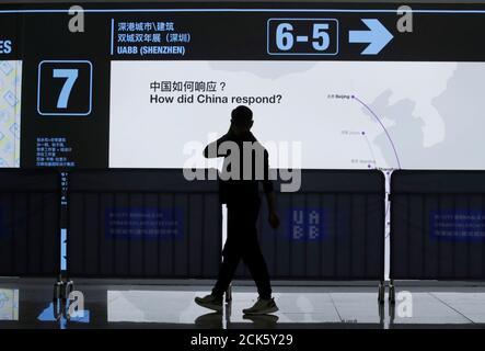 """Un homme passe devant l'exposition """"les yeux de la ville"""" dans le cadre d'une Biennale commune Hong Kong/Shenzhen d'Urbanisme et d'architecture à la gare de Futian à Shenzhen, Chine le 23 décembre 2019. Photo prise le 23 décembre 2019. REUTERS/Jason Lee"""
