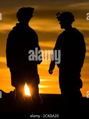 Les Marines du 3e Bataillon du 4e Bataillon parlent pendant le coucher du soleil à la base de Delaram dans la province de Nimroz, dans le sud de l'Afghanistan le 13 janvier 2010. REUTERS/Marko Djurica (AFGHANISTAN - Tags: CONFLIT MILITAIRE)