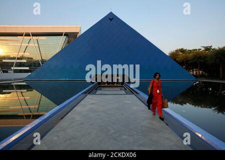 Un employé sort d'un bâtiment emblématique en forme de pyramide en verre sur le campus Infosys à Electronics City à Bangalore, le 28 février 2012. Photo prise le 28 février 2012. REUTERS/Vivek Prakash (INDE - Tags: EMPLOI DES ENTREPRISES SCIENCE TECHNOLOGIE) Banque D'Images