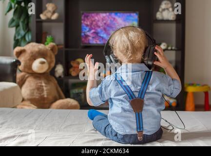 Joli petit garçon avec un casque regardant la télévision sur un canapé dans le salon à la maison
