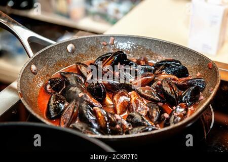 Les moules fraîches sont cuites dans une casserole dans une délicieuse sauce au vin crémeuse. Gros plan de la cuisson des moules dans un restaurant. Mise au point sélective