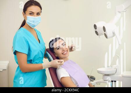 Portrait d'une femme dentiste souriante et sympathique avec un patient dans le bureau d'une clinique dentaire.