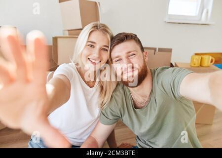 Jeune couple se déplaçant dans la nouvelle maison.assis sur le sol et faisant selfie