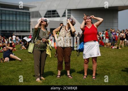 Les femmes regardent une éclipse solaire partielle au Musée de l'aviation et de l'espace du Canada à Ottawa (Ontario), Canada, le 21 août 2017. REUTERS/Chris Wattie