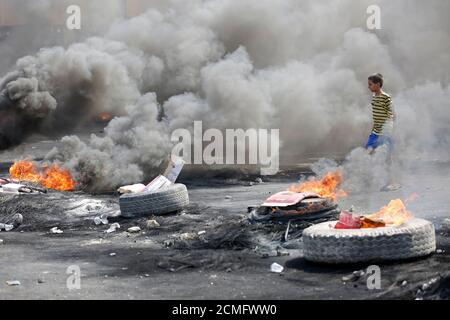 Un garçon est vu près de pneus en feu pendant un couvre-feu, deux jours après que les manifestations anti-gouvernementales dans tout le pays aient pris un caractère violent, à Bagdad, en Irak, le 3 octobre 2019. REUTERS/Wissm al-Okili
