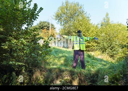 Taille de la vie vue inhabituelle sur la voie de campagne habillée par la police le fracas de l'officier portant un uniforme élégant dans le jardin devant, en hauteur veste de police Banque D'Images