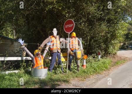Taille de la vie vue inhabituelle sur la voie de campagne habillée 3 des ouvriers debout, portant un uniforme élégant dans le jardin avant avec stop et une surprise Banque D'Images