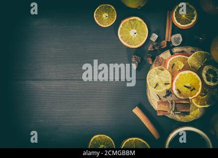 Dans une tasse de thé avec secs agrumes et d'épices sur une surface en bois noir Banque D'Images