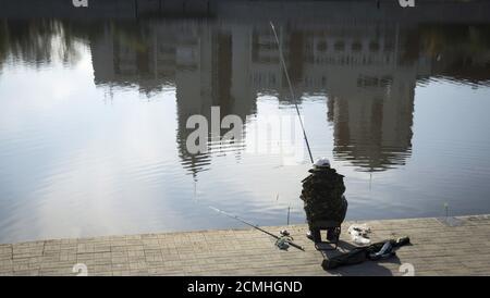 Un homme pêche sur un remblai de la rivière Ishim à Astana, Kazakhstan, le 11 octobre 2015. REUTERS/Shamil Zhumatov Banque D'Images