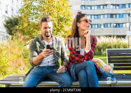 Une petite amie qui s'ennuie avec son smartphone.