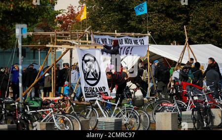 Les gens ont mis en place une bannière avec le symbole de la rébellion d'extinction (XR) dans un camp de militants du climat de fortune à côté du bâtiment du Reichstag à Berlin, en Allemagne, le 6 octobre 2019. REUTERS/Hannibal Hanschke