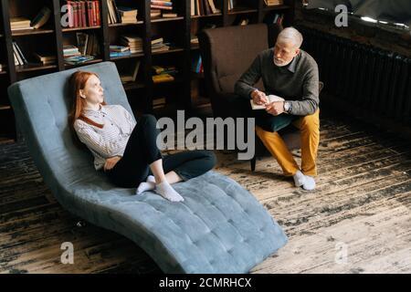 Jeune femme attirante dans un fauteuil parlant de ses problèmes avec un homme mature psychothérapeute