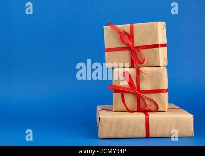 pile de boîtes enveloppées dans du papier brun et nouées avec un noeud rouge, cadeaux sur fond bleu Banque D'Images