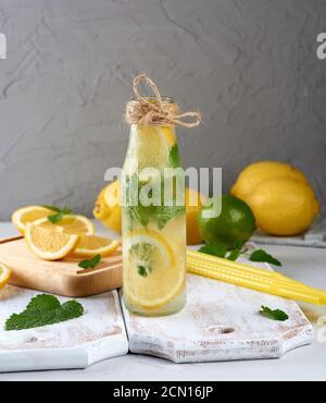 boisson rafraîchissante d'été limonade avec citrons, feuilles de menthe, citron vert dans une bouteille en verre