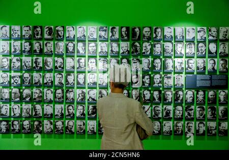 A visitor looks at pictures of co-conspirators of a 1944 coup attempting to overthrow Adolf Hitler at the German Resistance Memorial Centre, an exhibition about people who opposed the rule of the Nazis before and during World War II, in Berlin July 1, 2014. REUTERS/Thomas Peter (GERMANY - Tags: POLITICS TPX IMAGES OF THE DAY)
