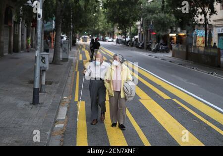 Un couple âgé portant un masque facial marche sur un trottoir marqué pour que les piétons gardent la distance sociale, pendant les heures où les personnes âgées sont autorisées à être à l'extérieur, comme la propagation de la maladie du coronavirus (COVID-19) continue, à Barcelone, Espagne, le 11 mai 2020. REUTERS/Nacho Doce
