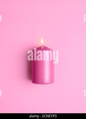 Bougie rose brûlante isolée sur un fond rose sans couture. Plat avec une bougie allumée. Une bougie aromatique de couleur rose, vue de dessus. Banque D'Images
