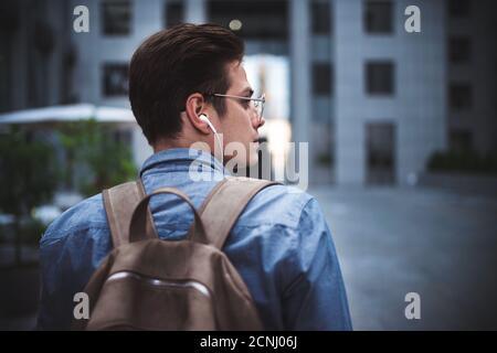 Portrait de jeune gai beau et beau homme bien habillé avec des écouteurs pensant au nouveau projet.