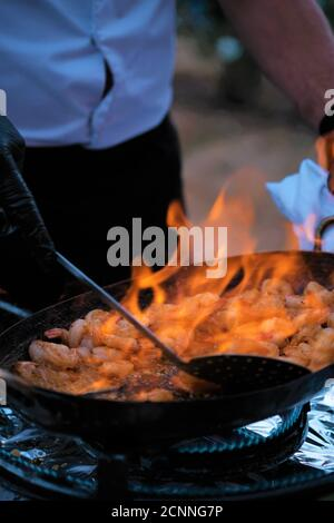 Gros plan d'un homme cuisant des crevettes flambeées, France