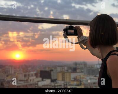 Gros plan photo d'une jeune femme photographe, tenant un appareil photo dans elle main