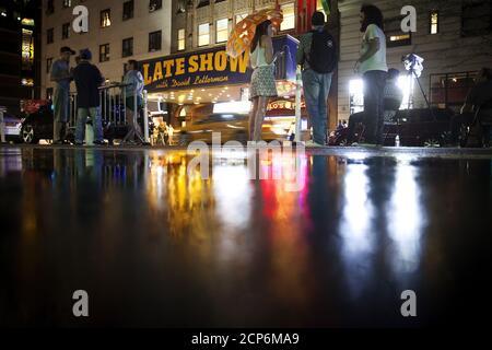 Les gens se tiennent et attendent qu'un équipage de signalisation retire le chapiteau de l'autre côté de la rue du Ed Sullivan Theatre où « The late Show » avec David Letterman a utilisé pour enregistrer dans le quartier de Manhattan à New York le 27 mai 2015. L'enregistrement et la diffusion de l'édition finale de « The late Show » ont eu lieu le 20 mai et les travailleurs transforment lentement le théâtre pour le nouvel hôte du spectacle, Stephen Colbert, qui sera présenté en première place le 8 septembre 2015. REUTERS/Carlo Allegri