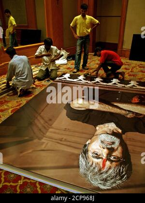 Les travailleurs indiens travaillent sur une affiche de l'acteur Bollywood Bachchan avant une conférence de presse d'un prochain film hindi 'SARKAR' à Bombay. Les travailleurs indiens travaillent sur une affiche de l'acteur Bollywood Amitabh Bachchan avant une conférence de presse d'un prochain film hindi 'SARKAR' à Bombay le 27 juin 2005. SARKAR est un film volatile traitant de la criminalité, de l'avidité, de l'amour, des relations familiales et de la retribution et s'inspire du classique « le parrain ». REUTERS/Adeel Halim