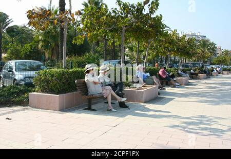 Couples retraités assis sur la Promenade Bench. Plage du Ponteil. Banque D'Images