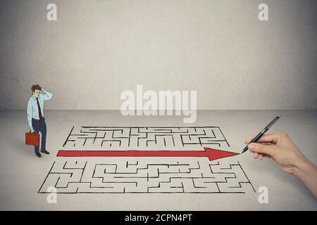 L'homme d'affaires à la main à l'élaboration de solution pour maze