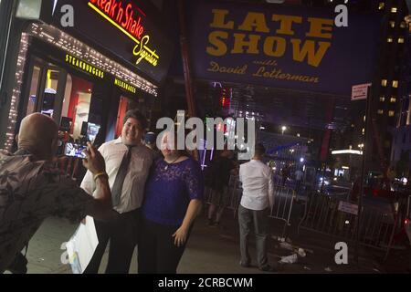 Les gens posent pour une photo tandis que les travailleurs retirent le chapiteau du Ed Sullivan Theatre où « The late Show » avec David Letterman a utilisé pour la bande dans le quartier de Manhattan New York le 27 mai 2015. L'enregistrement et la diffusion de l'édition finale de « The late Show » ont eu lieu le 20 mai et les travailleurs transforment lentement le théâtre pour le nouvel hôte du spectacle, Stephen Colbert, qui sera présenté en première place le 8 septembre 2015. REUTERS/Carlo Allegri