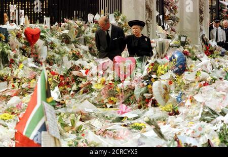 La reine Elizabeth de Grande-Bretagne et le duc d'Édimbourg regardent les hommages floraux rendus à l'extérieur du palais de Buckingham à la mémoire de Diana, princesse de Galles, Londres, dans ce fichier photo du 5 septembre 1997. La reine Elizabeth fête son 90e anniversaire le 21 avril 2016. REUTERS/Ian Waldie/fichiers RECHERCHEZ « Queen 90th » POUR TOUTES LES IMAGES