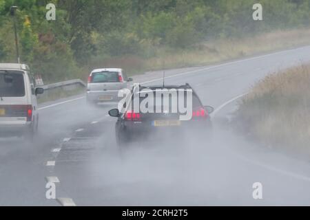 Les conducteurs qui conduisent des voitures sur une route à deux voies lors de fortes pluies avec une mauvaise visibilité en Angleterre, au Royaume-Uni. Mauvais temps et route humide et dangereuse en cas de pluie.