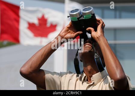 Un homme utilise des jumelles pour regarder une éclipse solaire partielle au Musée de l'aviation et de l'espace du Canada à Ottawa (Ontario), Canada, le 21 août 2017. REUTERS/Chris Wattie