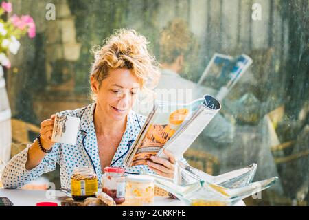 Blonde jeune femme mature en pyjama à la maison à l'heure du petit déjeuner, lisant un magazine et ayant une tasse de café