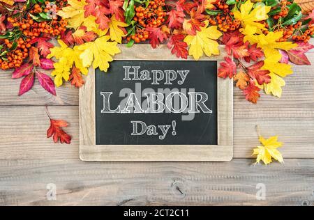 Bonne fête du travail ! Arrière-plan d'automne avec feuilles colorées et tableau noir