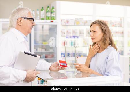 Une jeune cliente blonde touche son mal de gorge tout en lui demandant pour les médicaments
