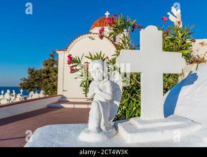 Statue d'ange et de Croix de prière avec église traditionnelle avec dôme rouge en arrière-plan, île de Karpathos, Grèce Banque D'Images