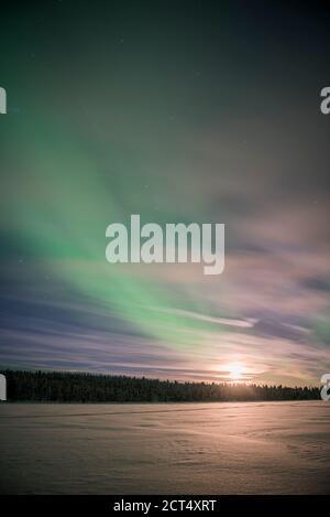 aurores boréales (aurora borealis) et lune, vue sur un lac enneigé en hiver en Laponie finlandaise, à l'intérieur du cercle arctique en Finlande Banque D'Images