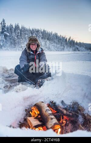 Personne assise à un feu de camp se réchauffant lui-même par un froid glacial en hiver dans le cercle arctique de Laponie, en Finlande