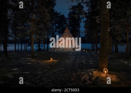 Expérience unique de voyage de camping dans une tente de cloche de Kota dans la forêt dans un paysage couvert de neige d'hiver merveilleux avec des bougies la nuit en Laponie, Finlande, cercle arctique