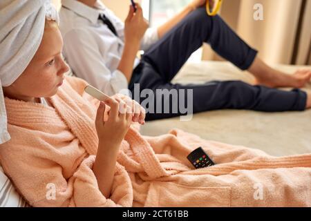 beau couple d'enfants commence la journée ensemble, fille et garçon se reposent sur le lit, repos