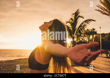 Athlète sportive et belle jeune femme s'étire et respire après faites de l'exercice en plein air avec le coucher du soleil et la lumière du soleil en arrière-plan avec océan et ciel - guérir