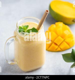 Smoothie à la mangue, lassi à la mangue dans un pot en verre avec de la paille de bambou
