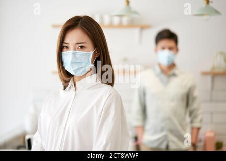 portrait d'une jeune femme asiatique portant un masque regardant appareil photo avec femme en arrière-plan