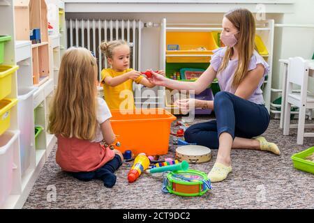 Jeune femme thérapeute portant un masque facial protecteur jouant avec deux jeunes filles pendant la thérapie professionnelle de l'enfant.