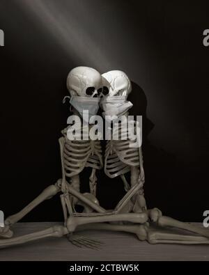Deux squelettes humains sont assis ensemble dans une pièce sombre portant des masques pour un étrange concept de santé du virus pandémique.