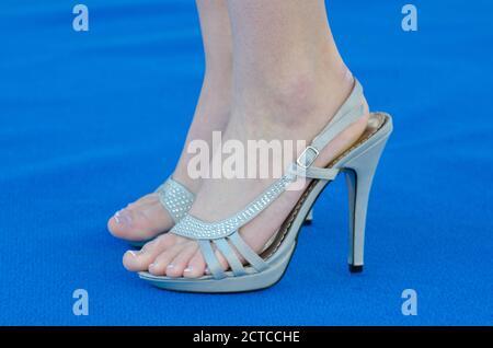 Pieds de dame avec chaussures Eegant à talons hauts sur fond bleu.