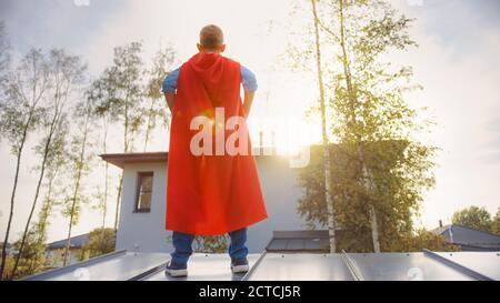 Garçon joue un rôle de Super Hero. Il est debout sur le toit d'une maison avec ses mains à la taille. Le jeune homme porte une cape rouge vif. Il l'est